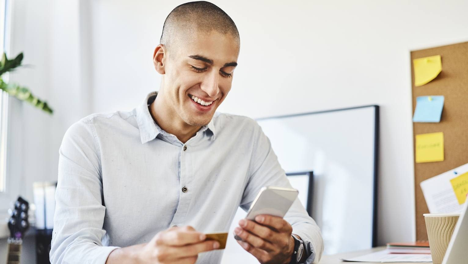 Young man sitting in home office paying online with credit card and smartphone.