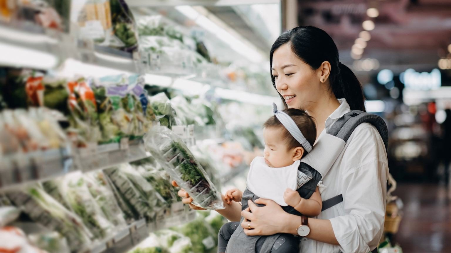 Mum with baby shopping for lettuce at supermarket.