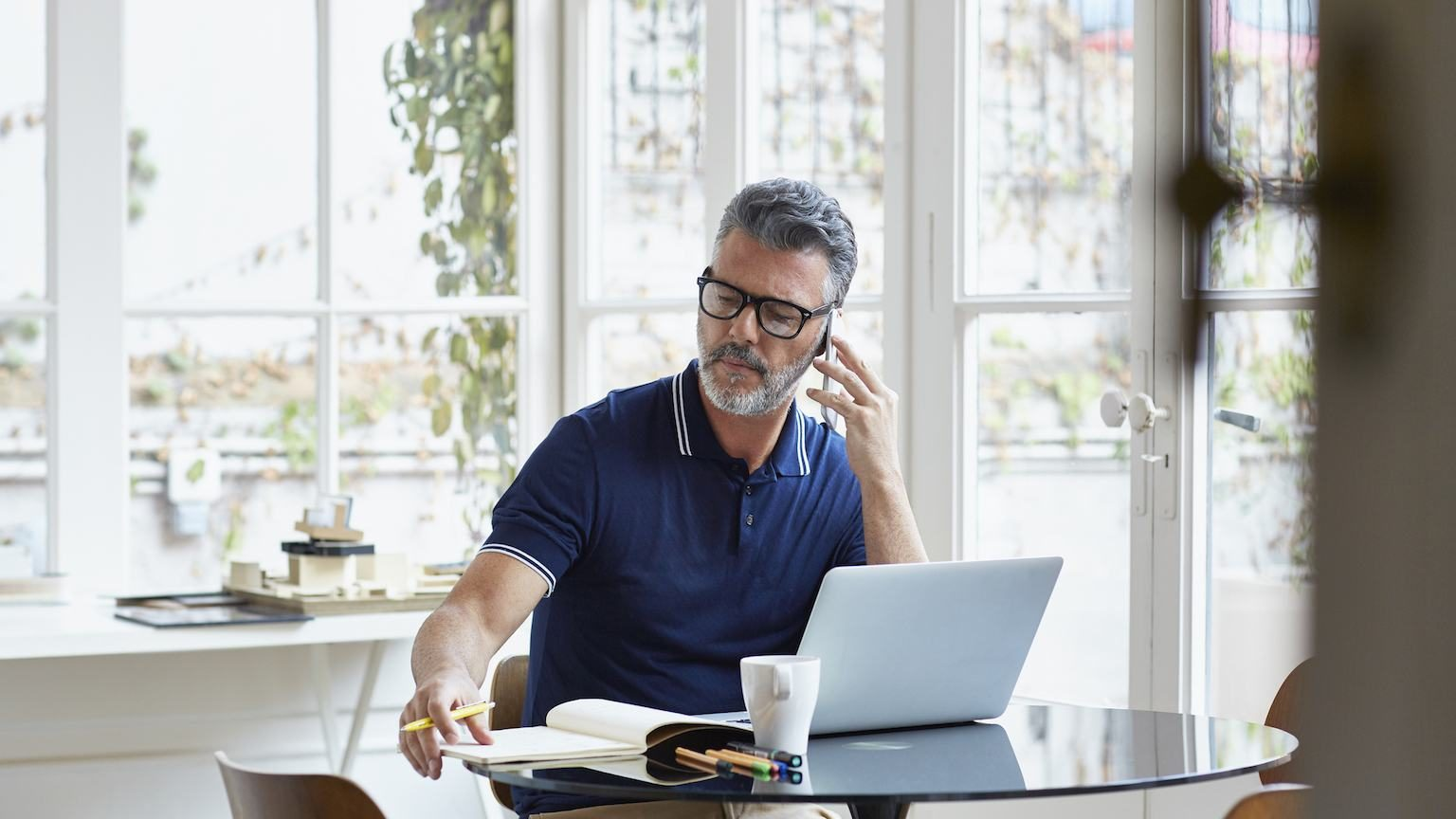 Man sitting at office table in front of laptop and on the phone.