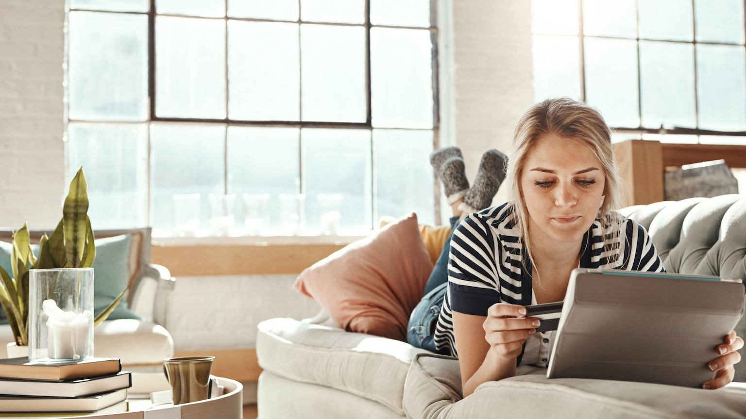 Young lady laying down on couch holding credit card and tablet.