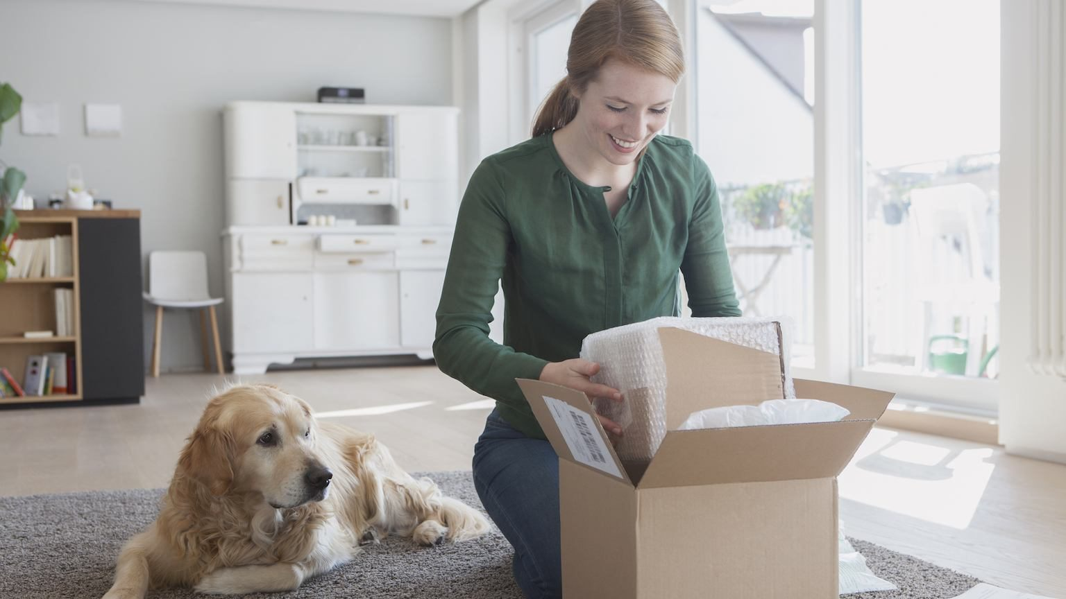 Lady opening online shopping delivery with pet dog by her side.