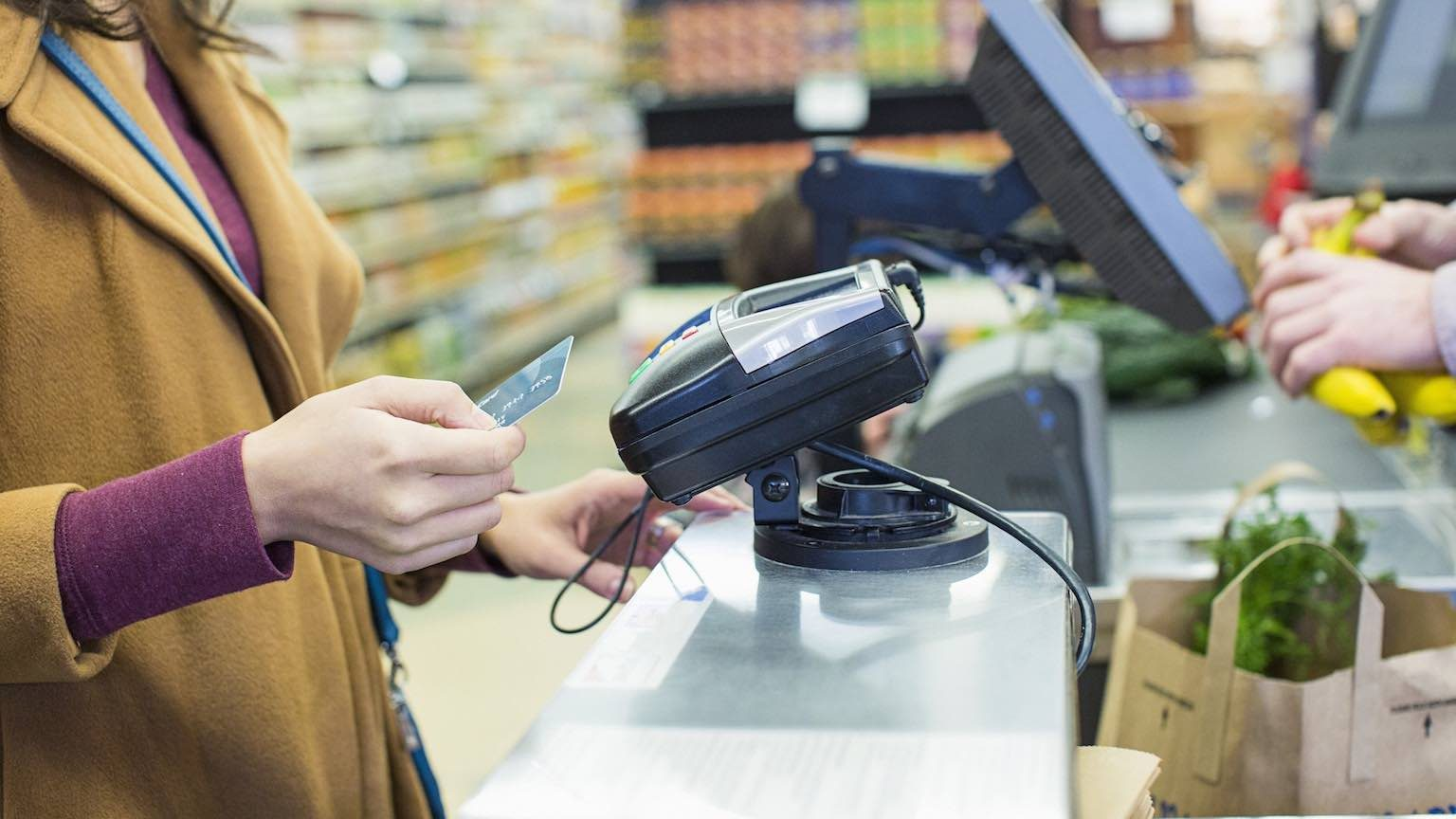 Lady using credit card to pay at supermarket EFTPOS terminal.