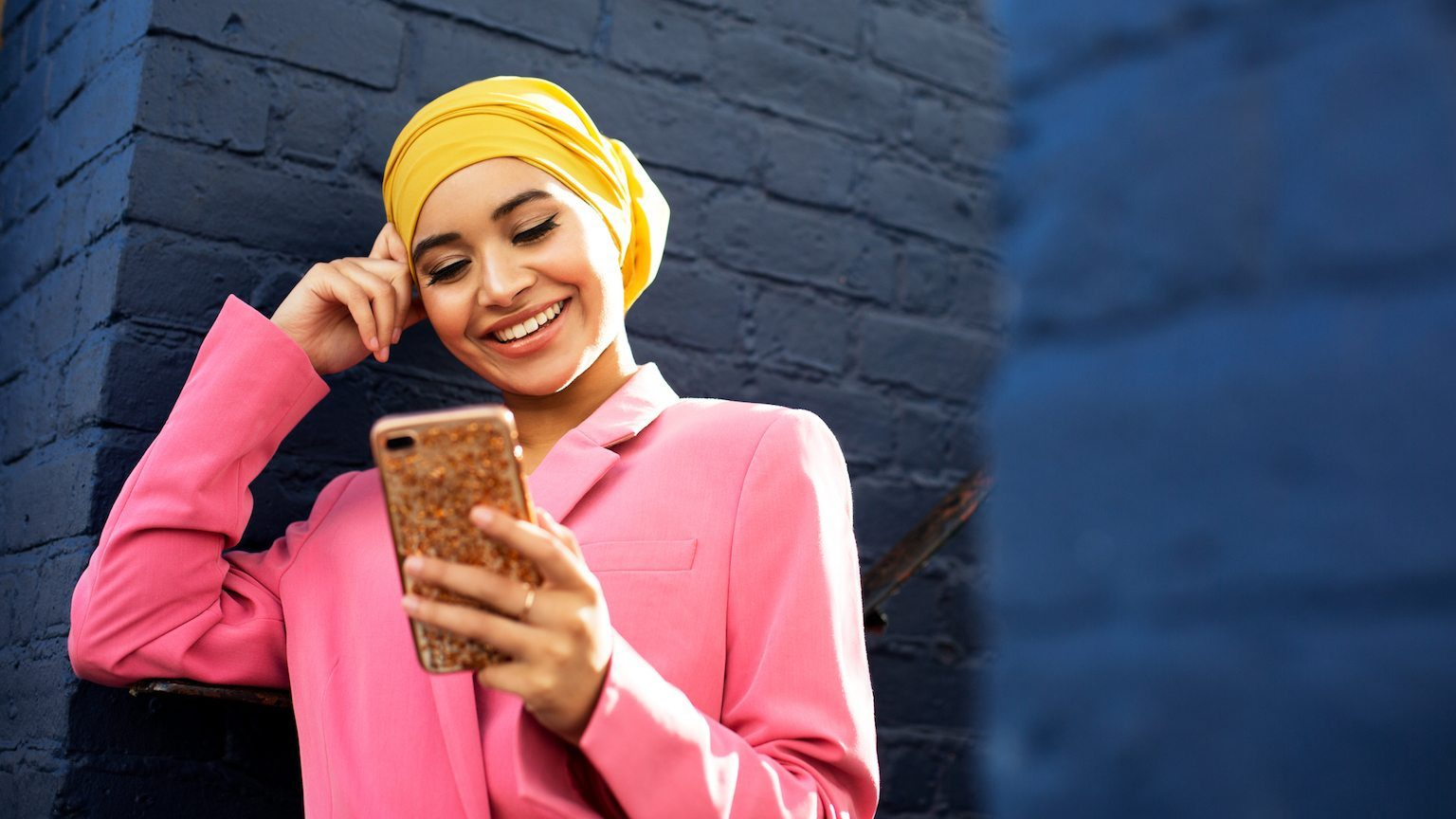 Young lady checking phone and smiling.