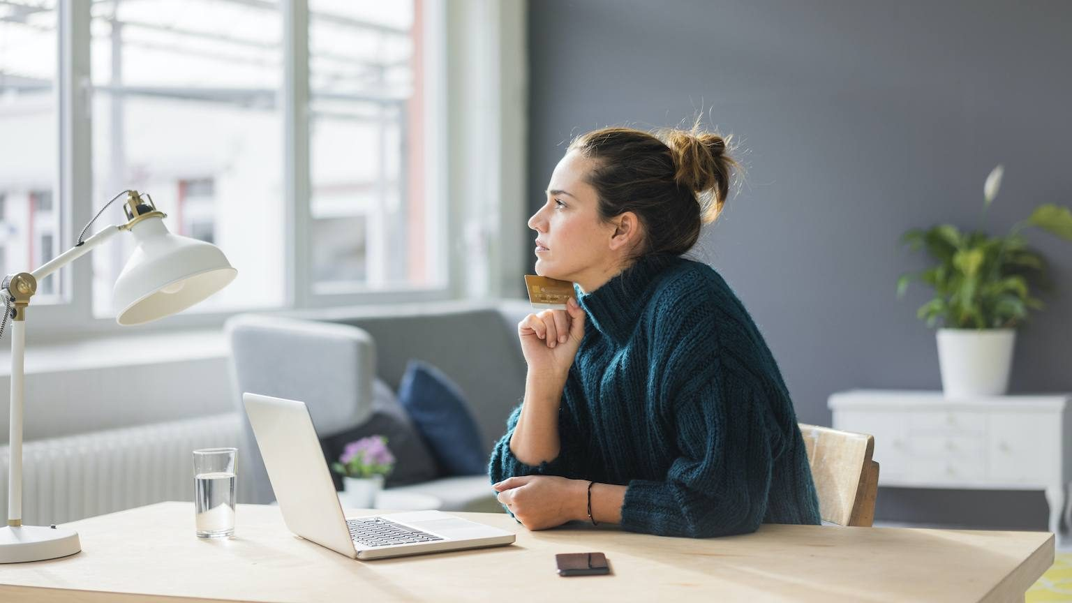 Lady sitting at desk with credit card in front of laptop.