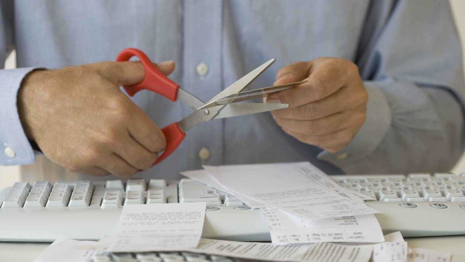 Man's hands cutting up credit card.