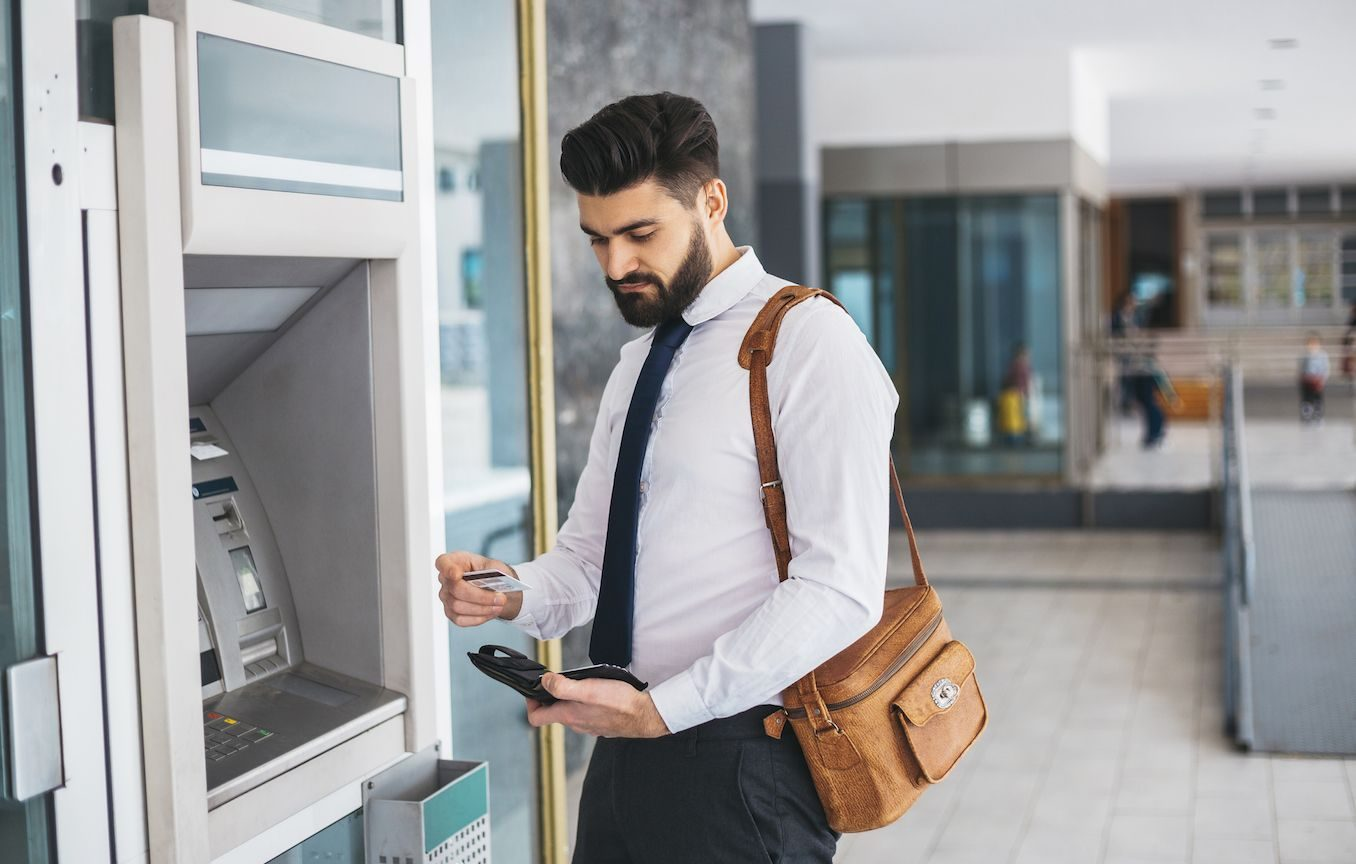 Man in suit getting card out of wallet at an ATM.