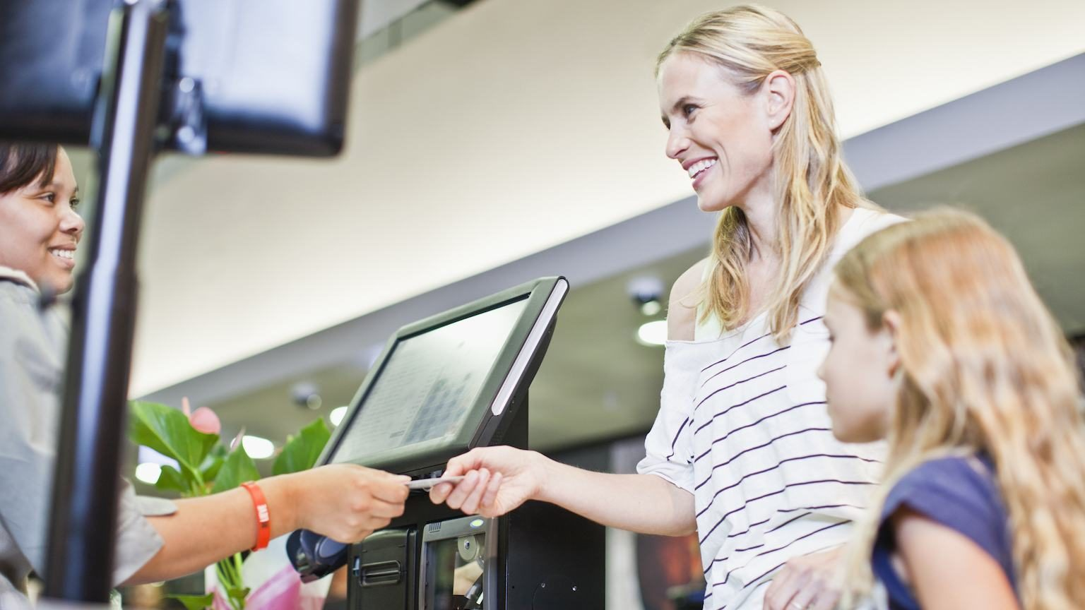 Mother and daughter paying for groceries with credit card.