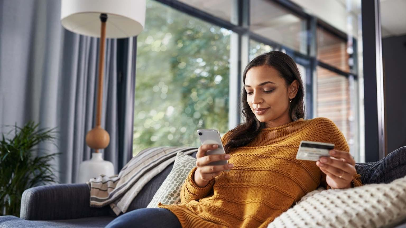 Lady sitting on couch, online shopping on smartphone with credit card.