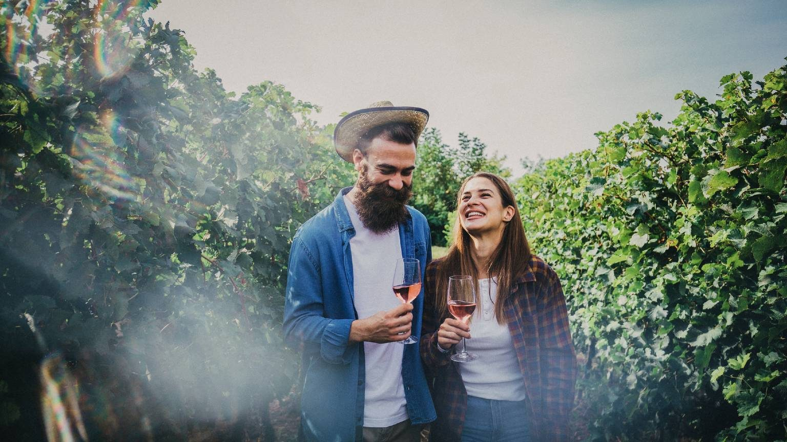 A handsome young couple tasting some wine in a vineyard on a sunny day.