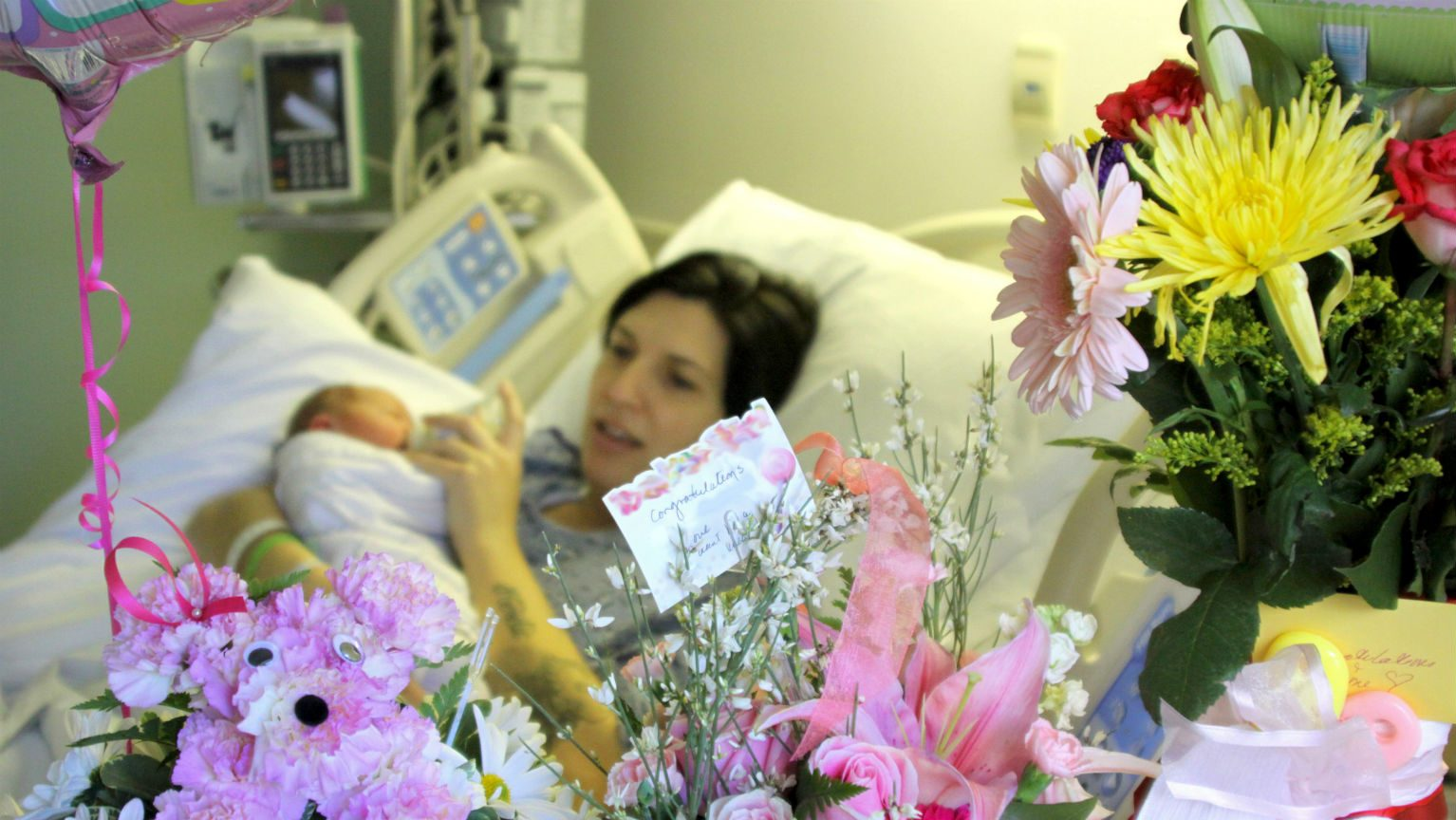 Woman and baby in hospital room surrounded by flowers
