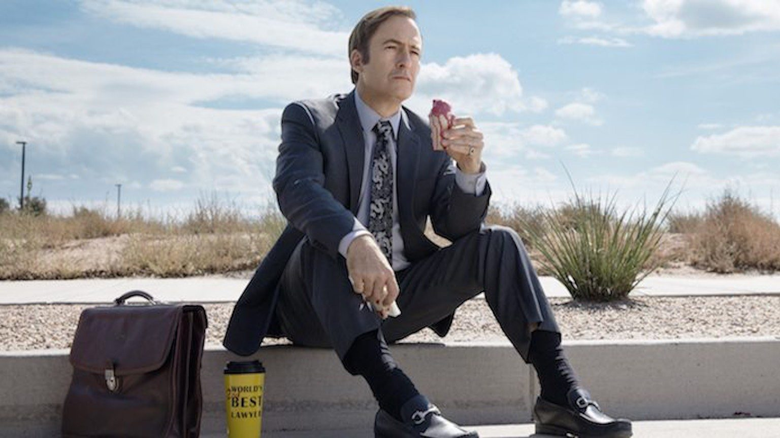 Saul Goodman, sitting on the gutter with his briefcase and coffee eating a donut