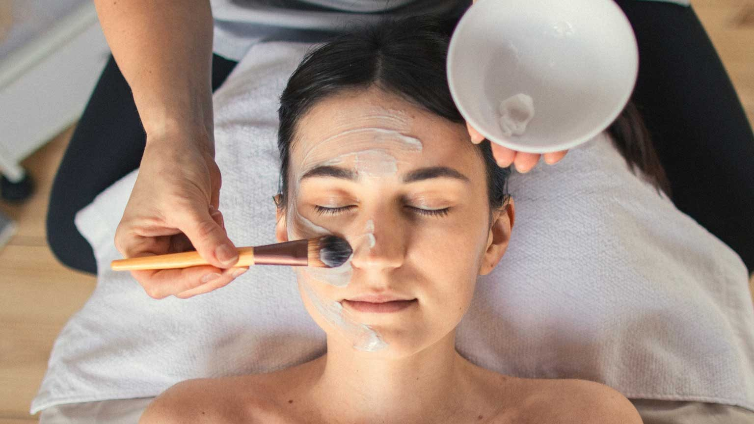 Applying Facial Mask To Woman In Spa