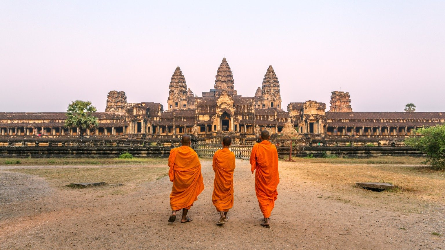 Three monks standing outside Angkor Wat.