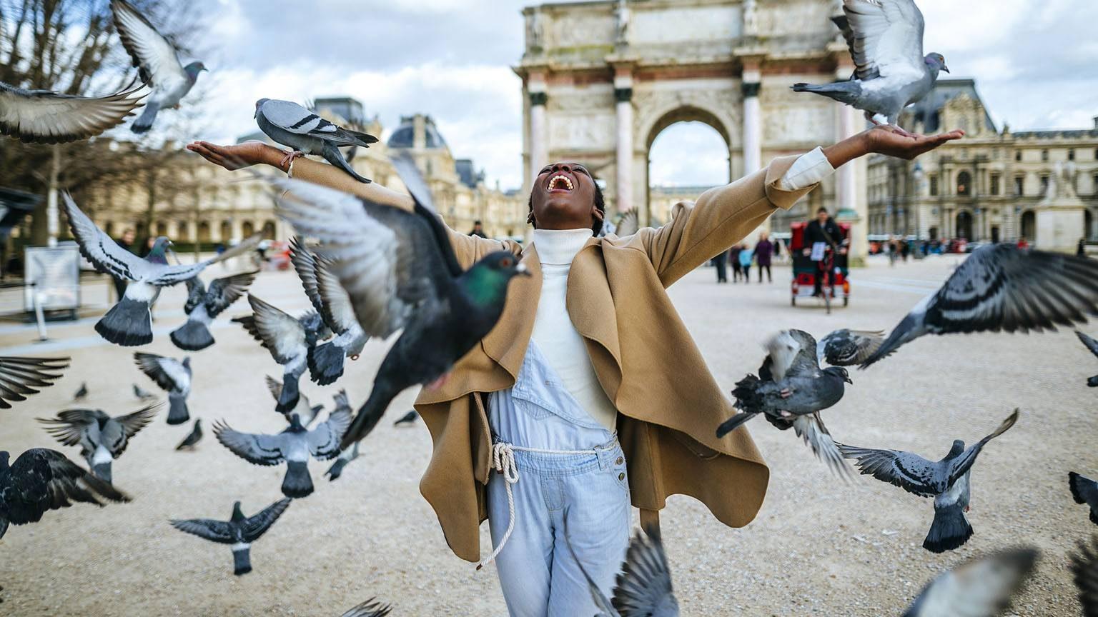 Happy woman with flying pidgeons