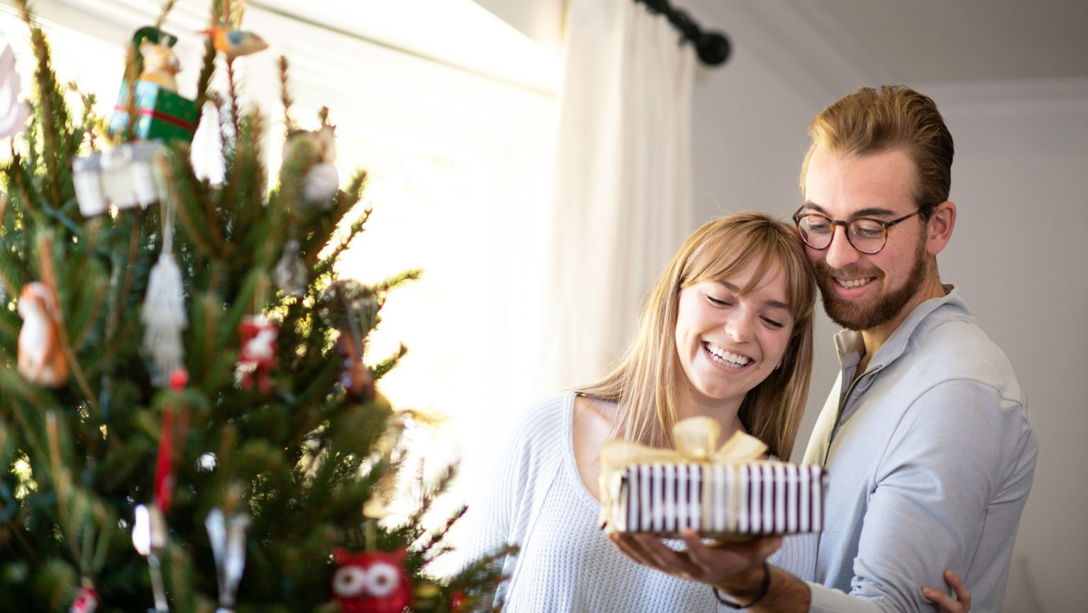 Couple with present next to Christmas tree