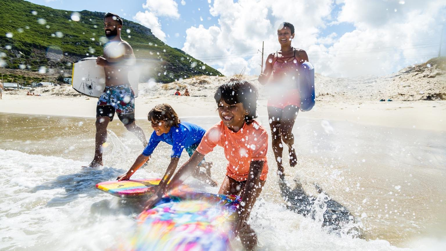 Family of four with body boards running into the ocean.
