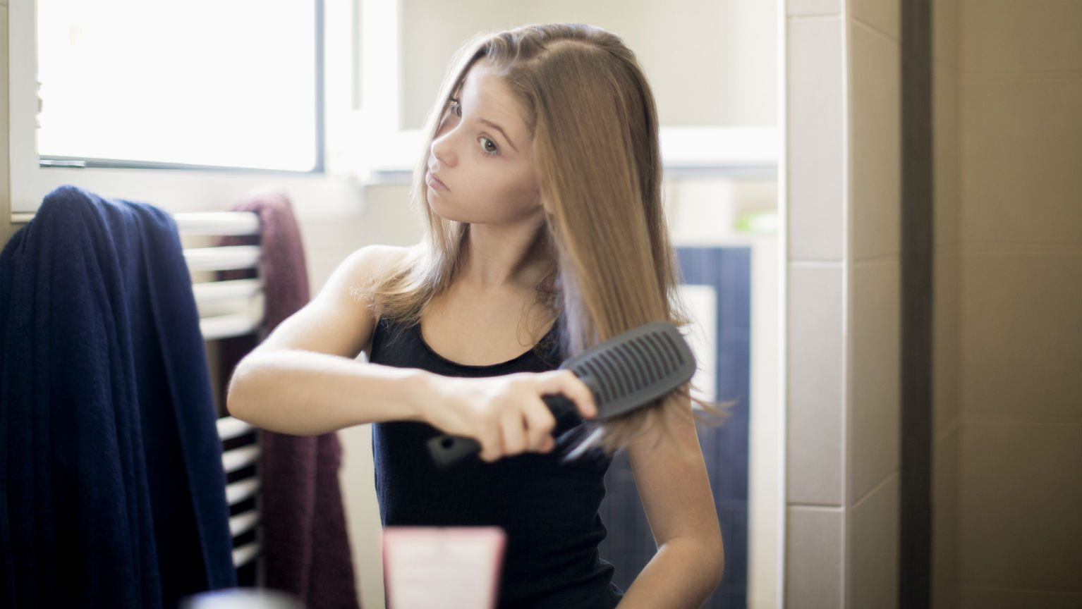 Teenage girl brushing hair