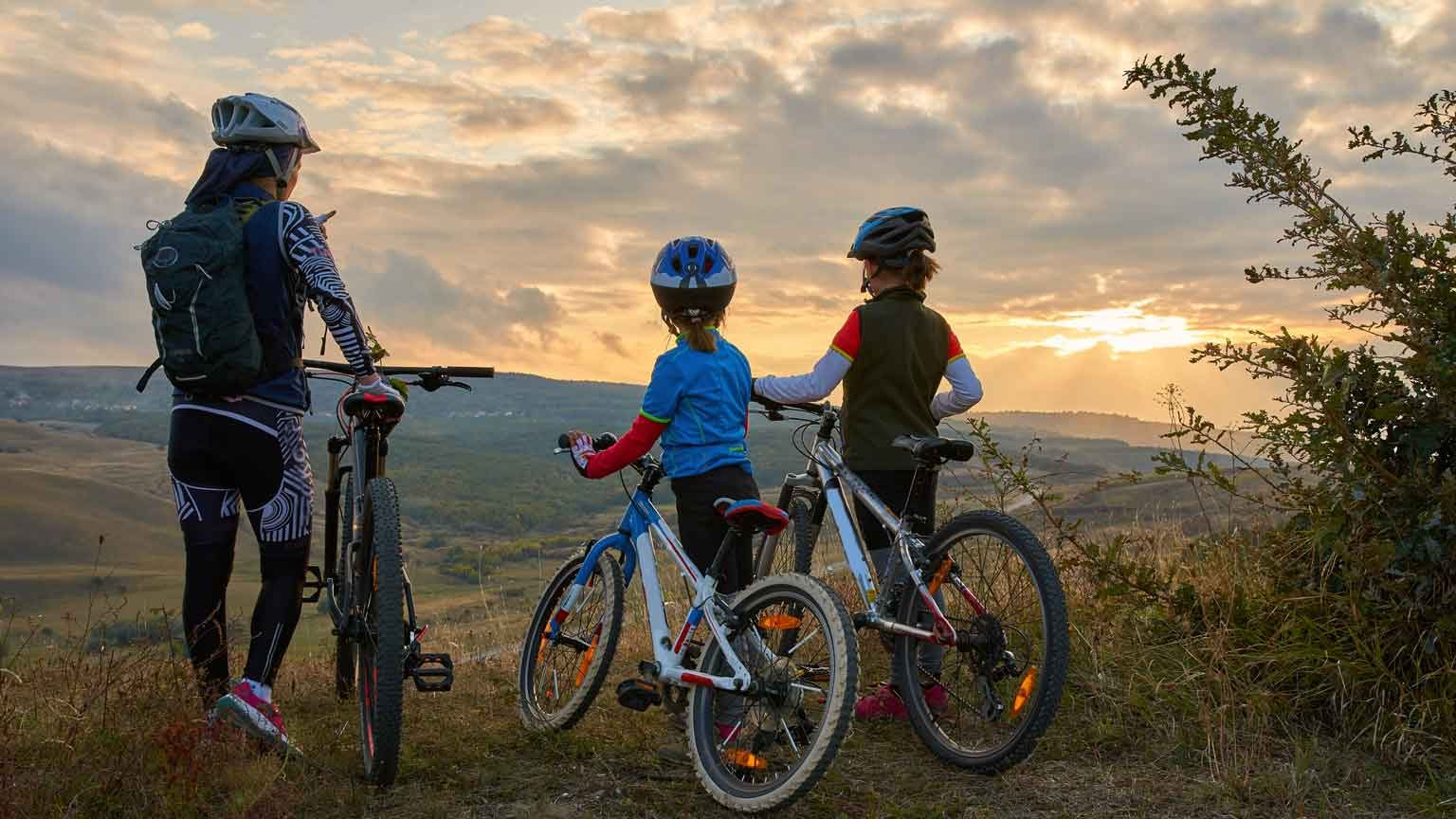 mountain bike family, outdoors have fun together on a summer afternoon sunset, cycling girls activity