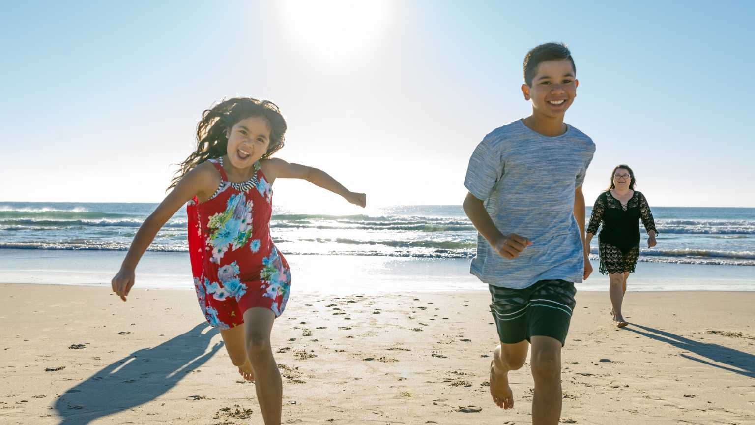 Pair of kids running on the beach with their parents/caregivers behind them.