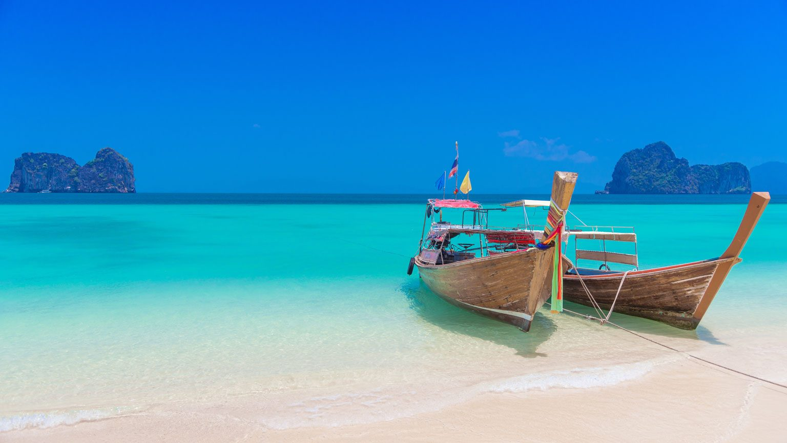 Two long tailed boats parking on the beautiful beach at Koh Hai, Trang province, Thailand.