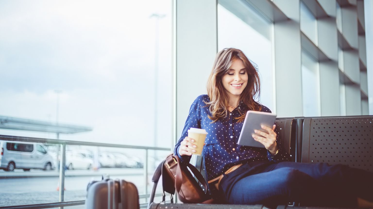 Woman looking at tablet and holding a coffee while waiting in airport.