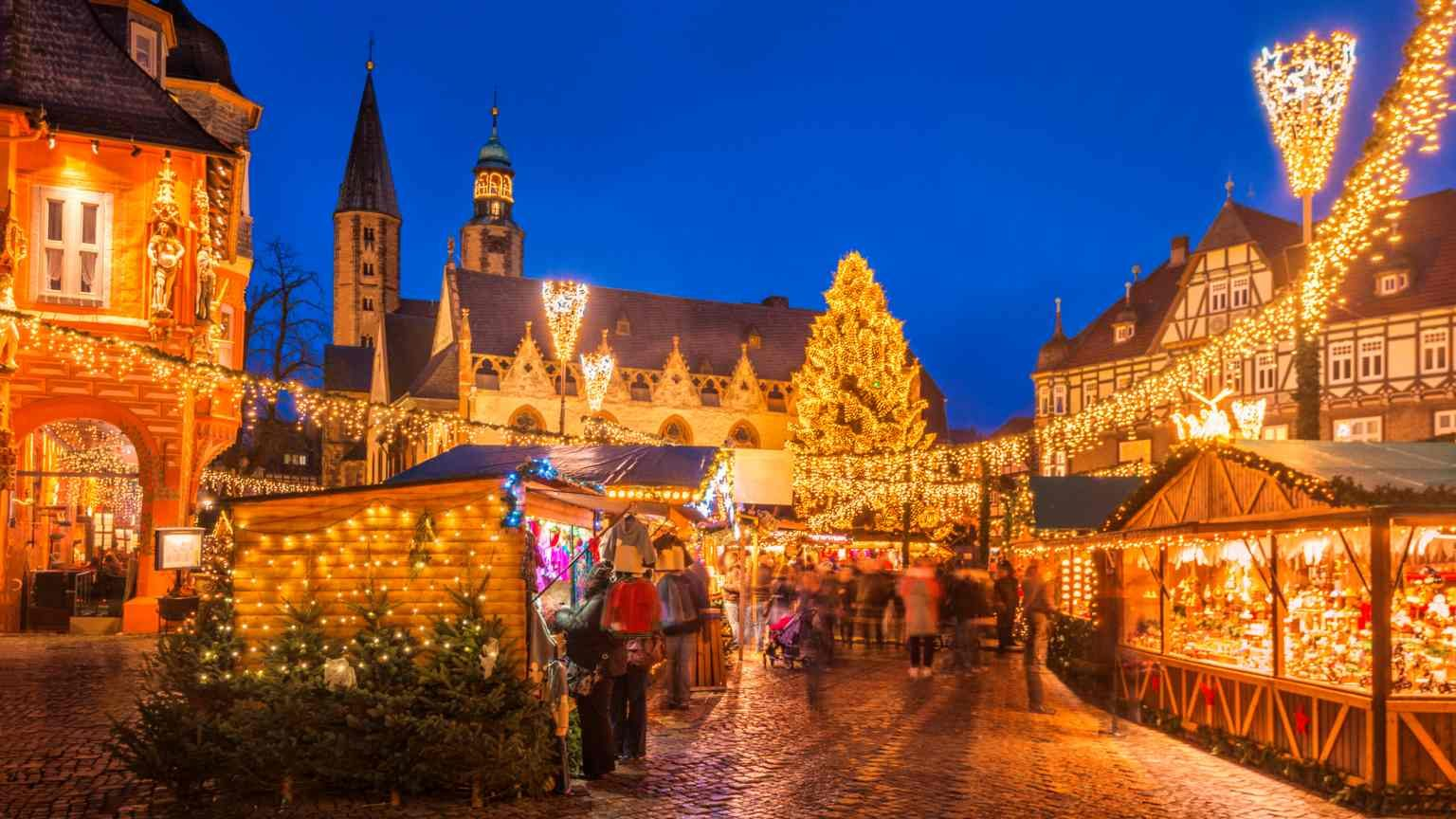 The traditional Christmas Market on the historic Market Square of Goslar, Germany at dusk.