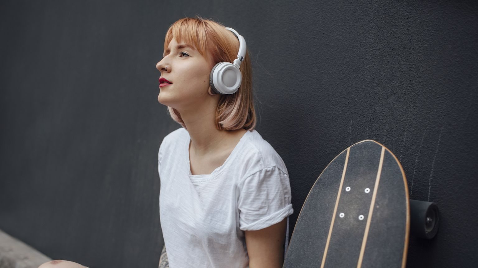 A woman wearing white over-ear wireless headphones, sitting next to her skateboard