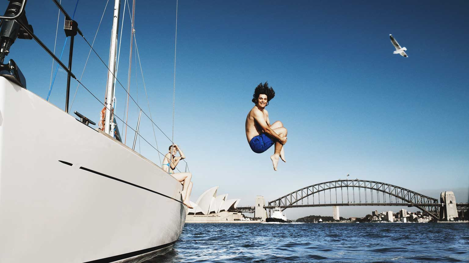 Australia, Sydney, young man jumping from boat in to harbour