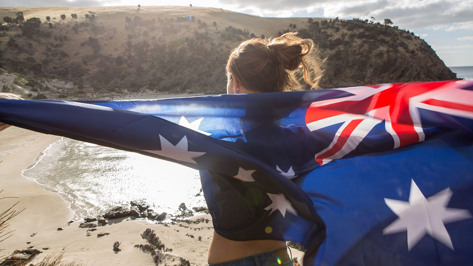 Cheerful young woman stands on a cliff above a beach in Kangaroo Island holding an Australian's flag.