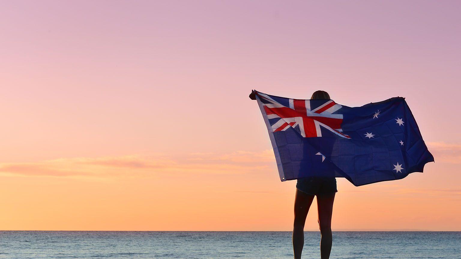 Waving the Australian Flag, evening summer light on a beach.
