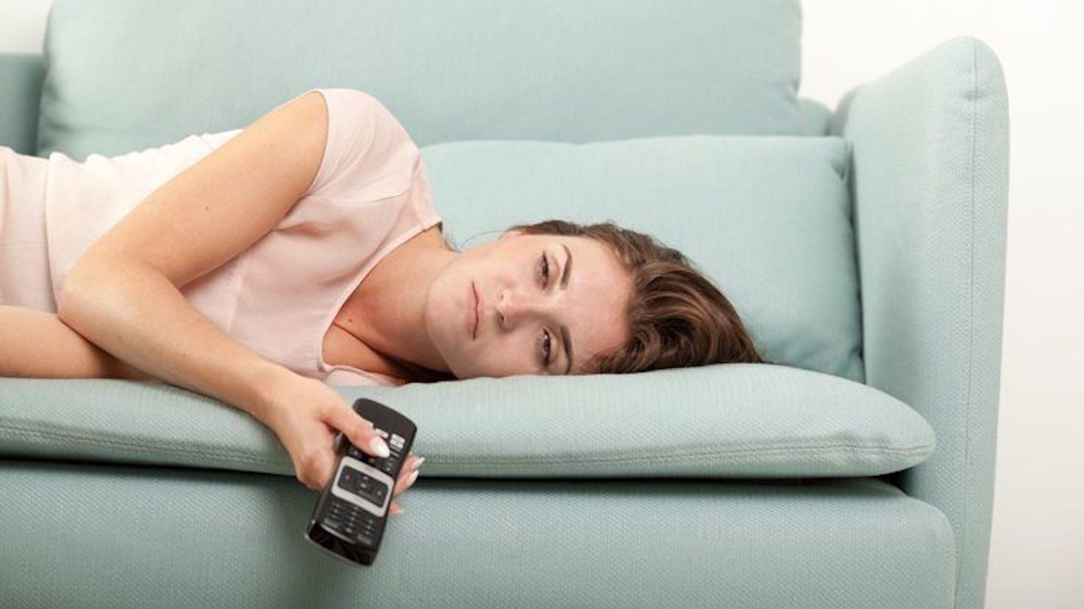 Bored woman on sofa watching TV