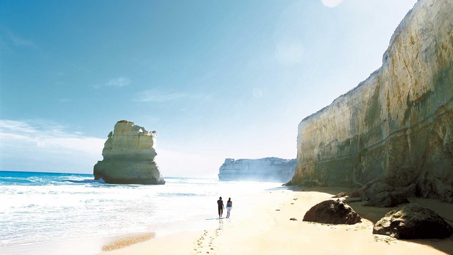 Couple walking down the beach at the Twelve Apostles.