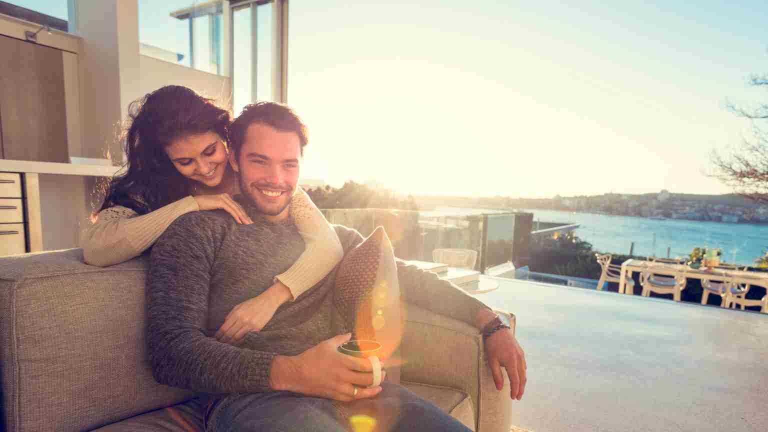 Couple on the sofa in the morning. He is drinking coffee and she is embracing him. They are happy and smiling. There is a view of the water in the background of this luxury home. Back lit with lens flare. (Couple on the sofa in the morning. He is drin