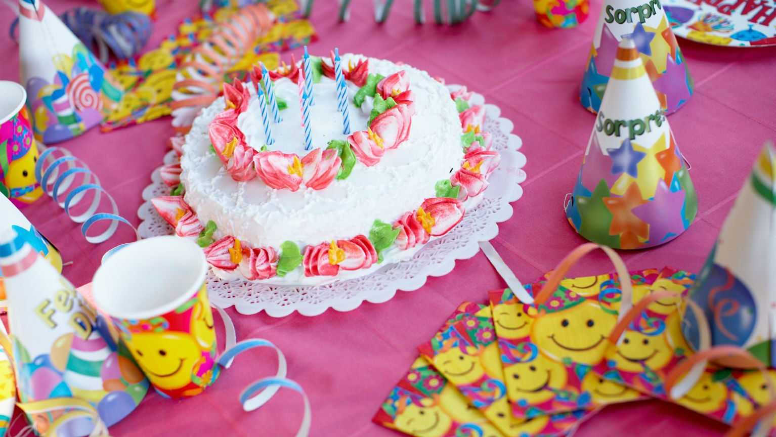 Birthday cake and party supplies on table