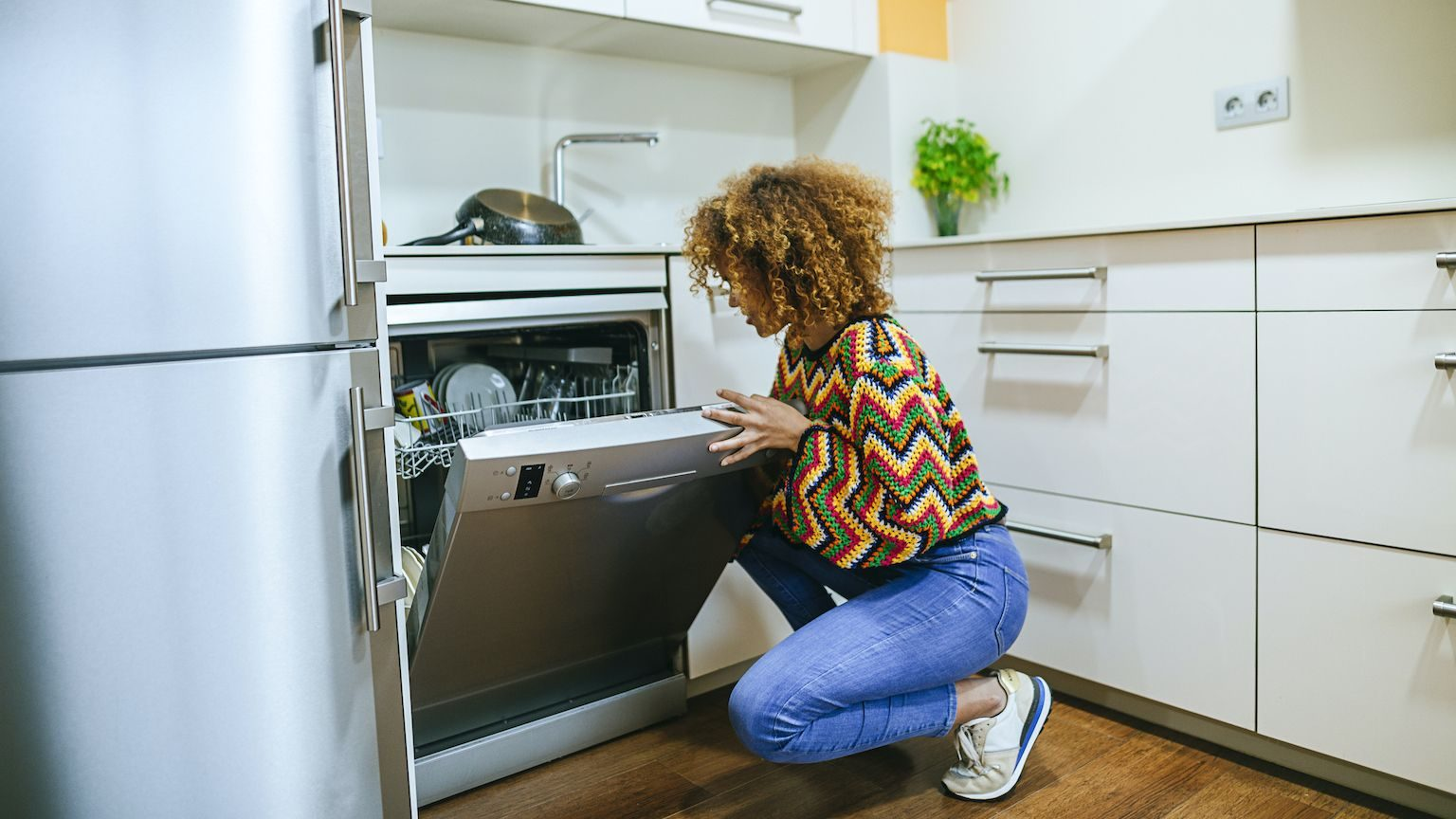 A young woman wearing a colourful sweater loading her dishwasher