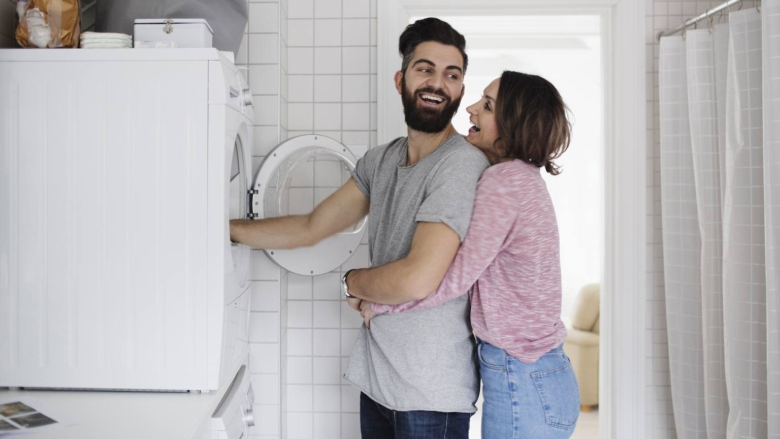 Happy couple putting clothes in washing machine.