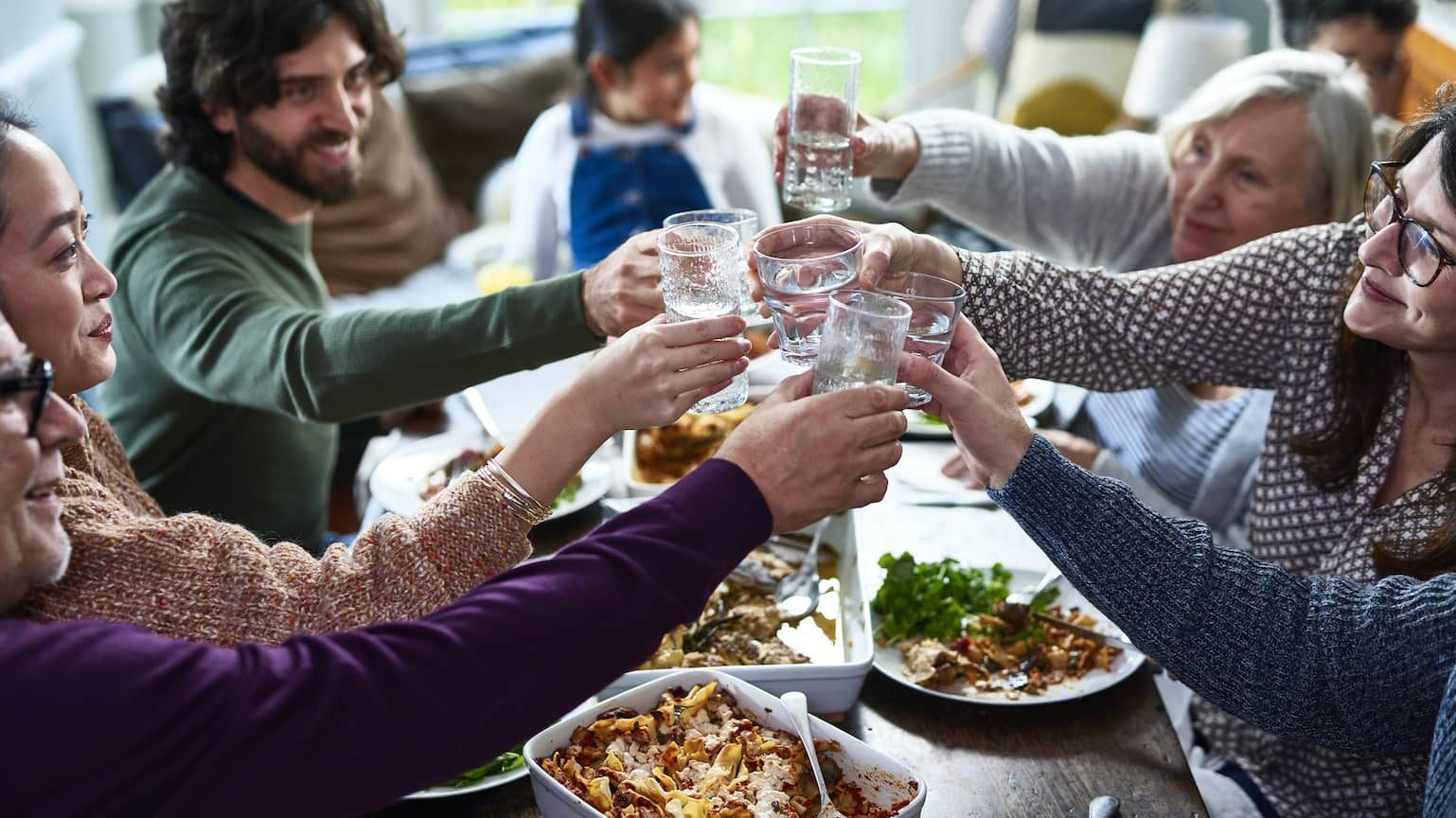 Family holding up water glasses to toast over a large meal.