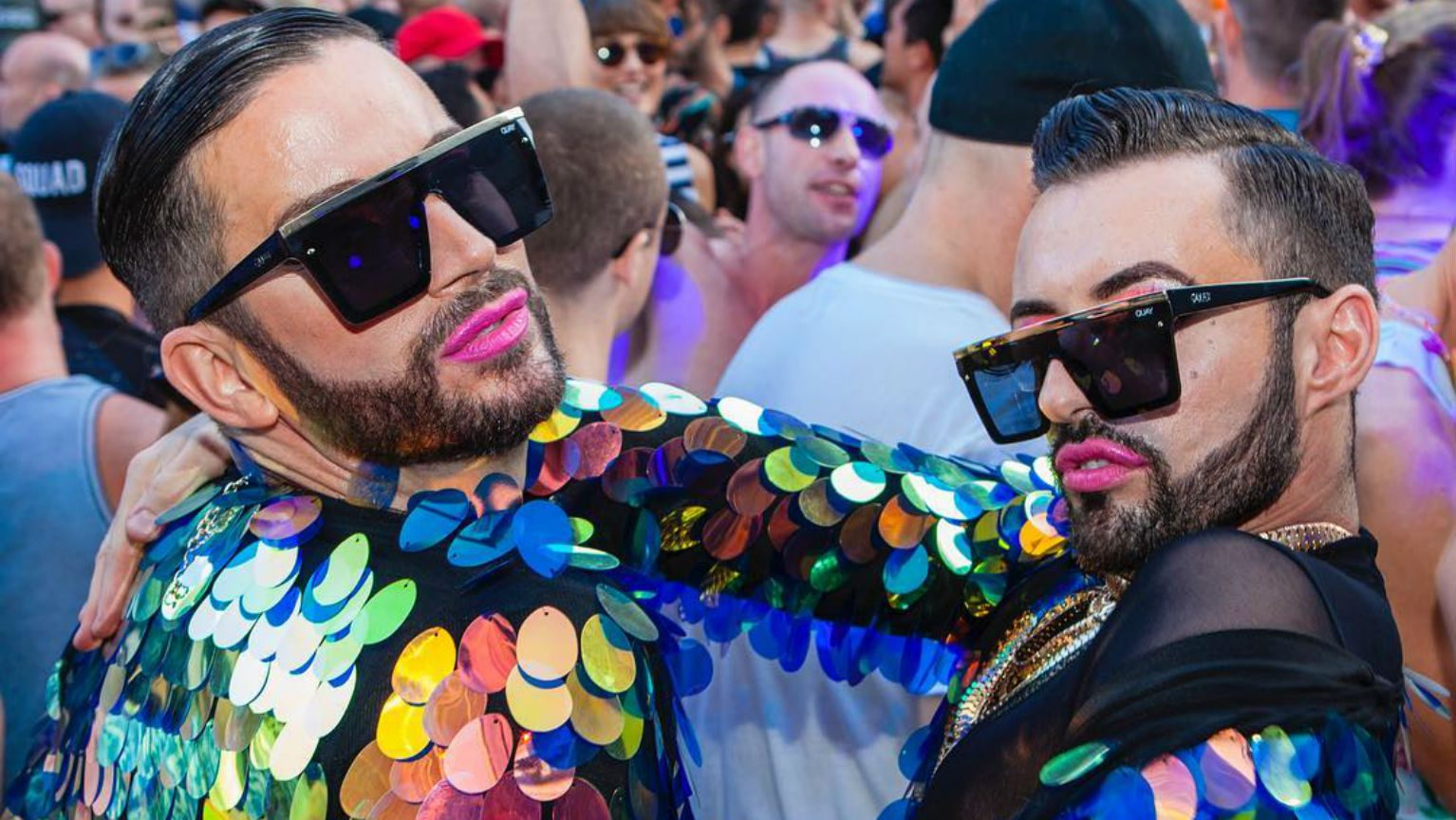Two men at Mardi Gras in rainbow sequinned jackets