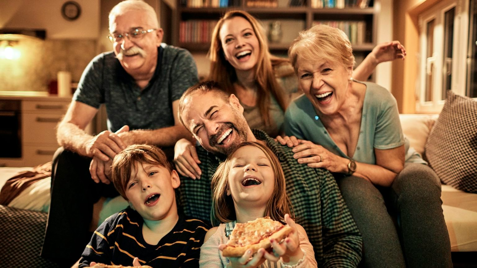 Close up of a multi generational family watching television