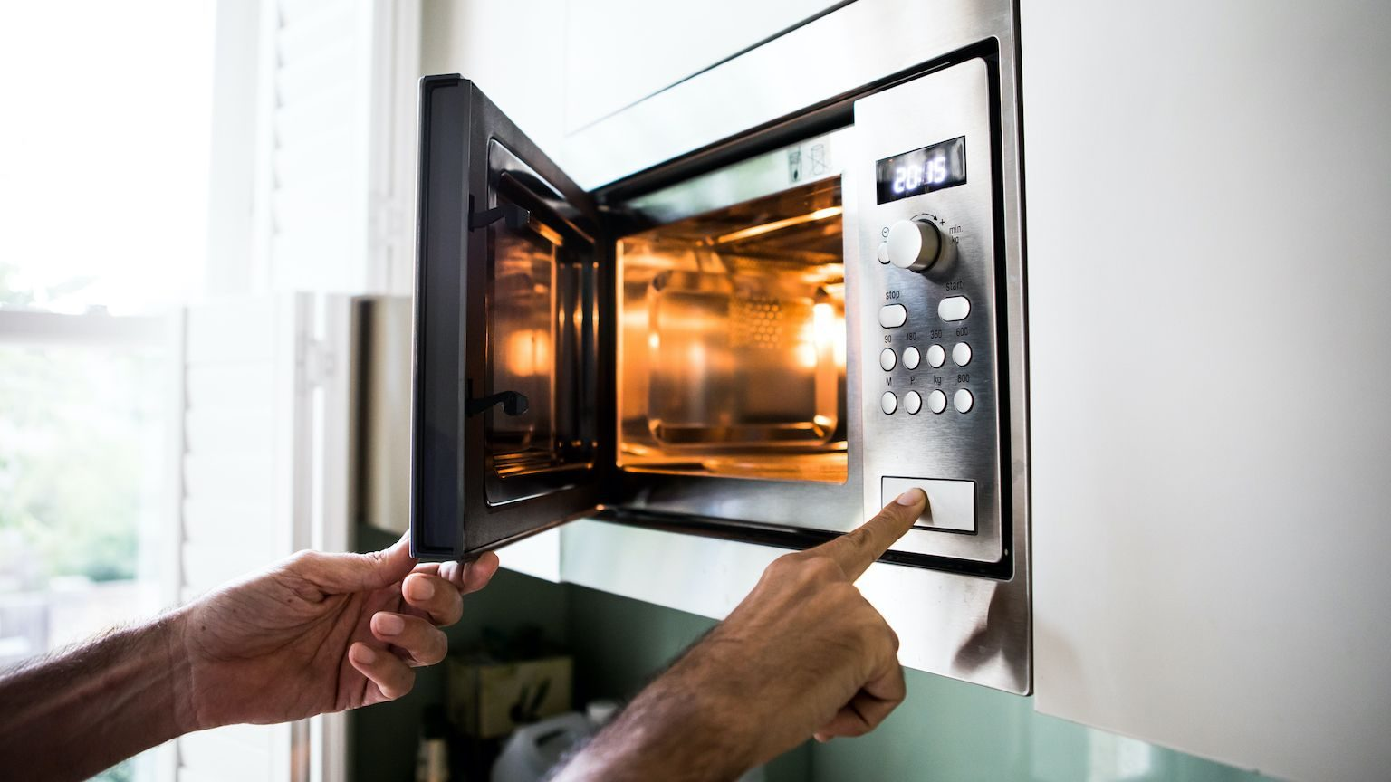 A mans hands opening a microwave and pushing buttons