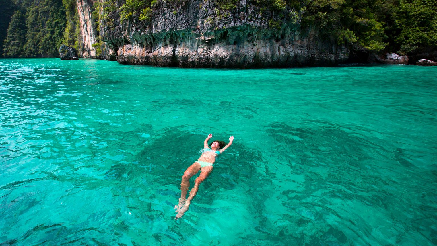 A woman relaxes while floating on her back in the warm turquoise waters of Thailand.