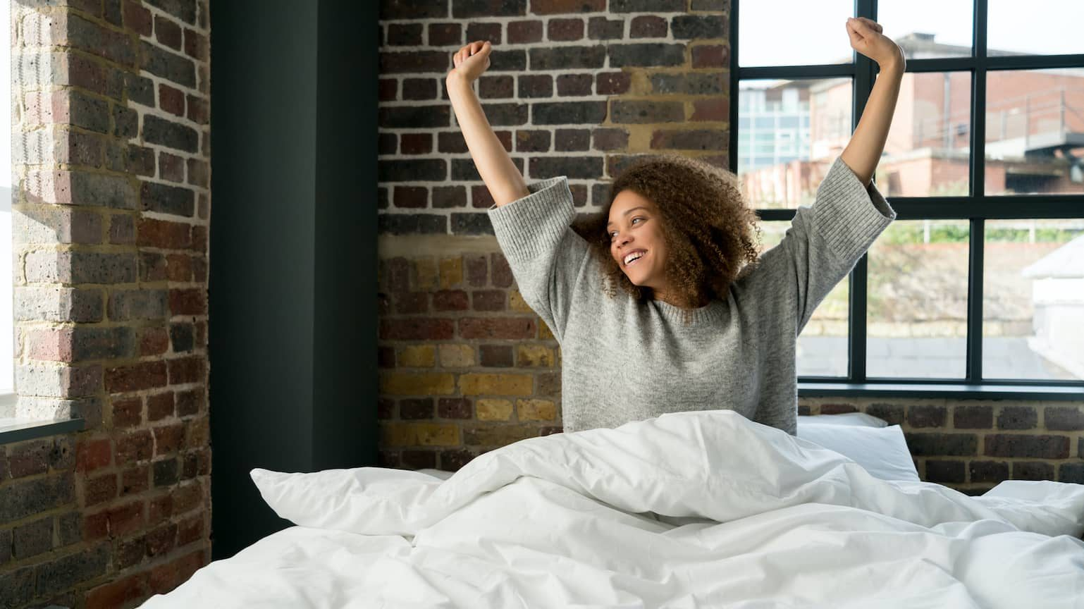 Woman waking up and stretching on a comfy mattress