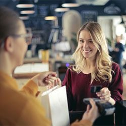 blonde woman paying using credit card at the counter