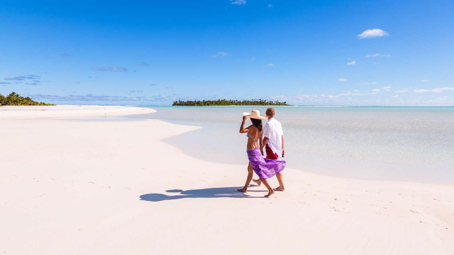 Couple walking on a beach in the Cook Islands
