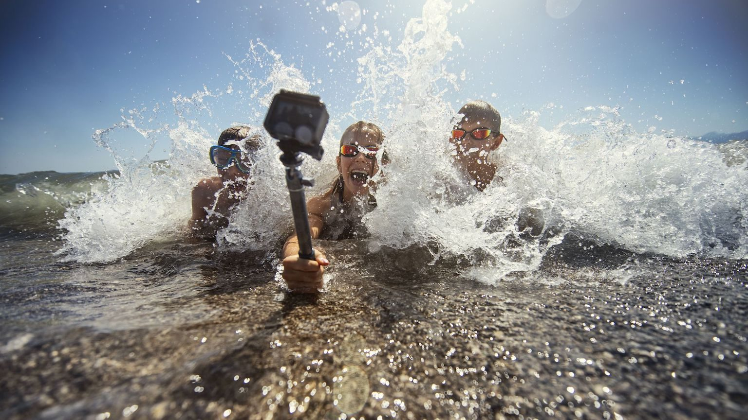 Three kids using an action camera to record themselves splashing in the surf