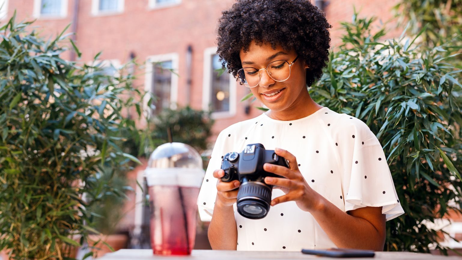 A young woman looking down at her digital camera and drinking a red juice