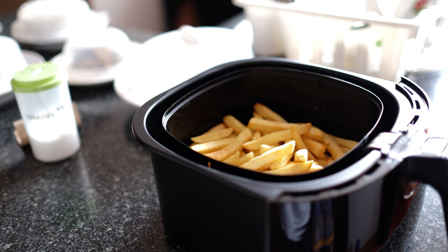 Close up of an air fryer filled with chips.