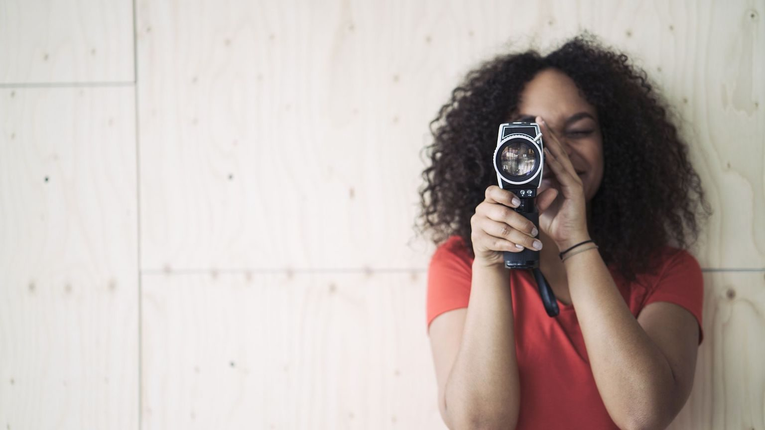 A young woman holding a vintage video camera