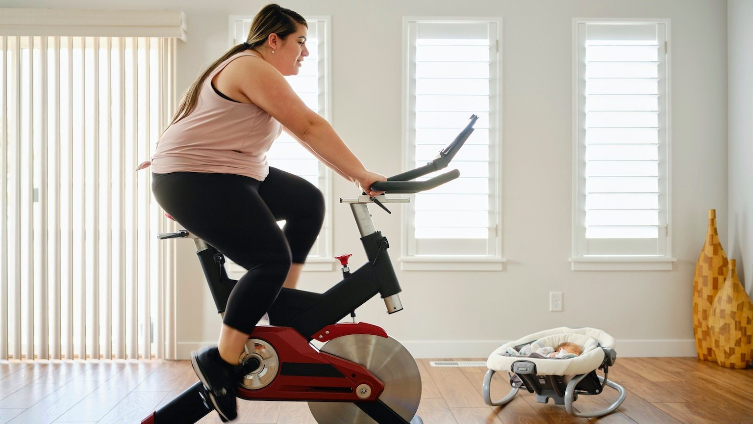 A young mother exercising in her home on an exercise bike.