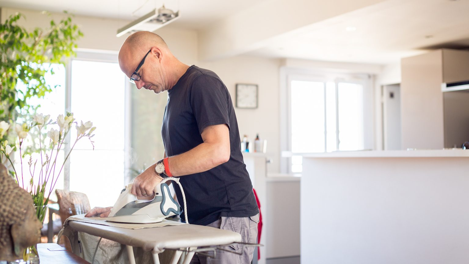 Man using an iron on an ironing board at home